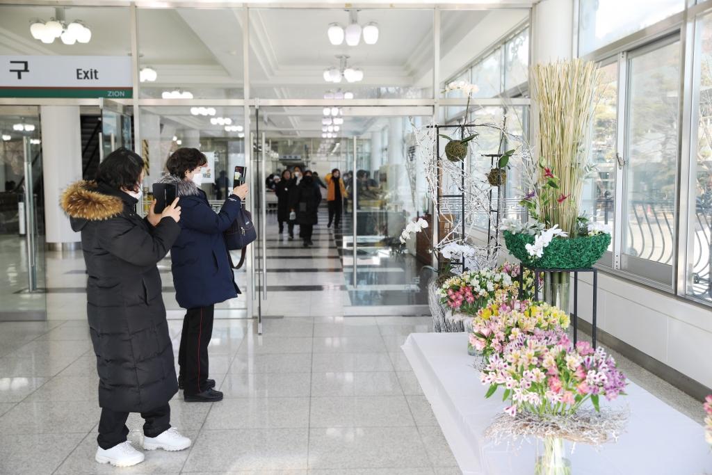 종합식당 출구에 설치된 꽃꽂이를 사진에 담는 사람들.